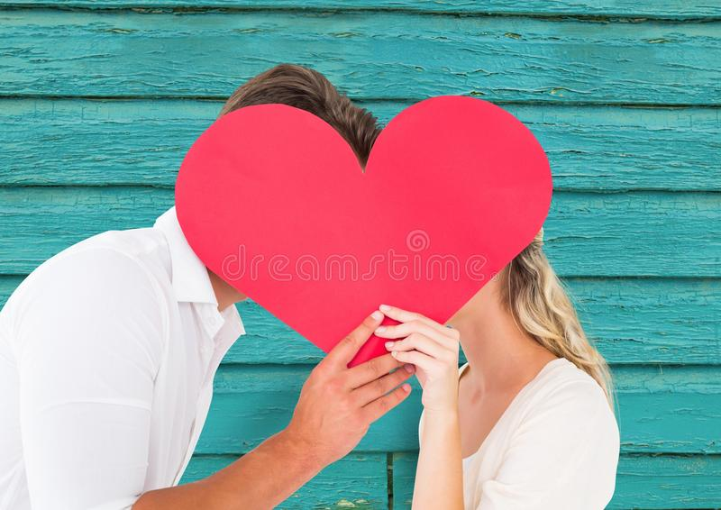 couple kissing behind the heart with light blue wood background stock images