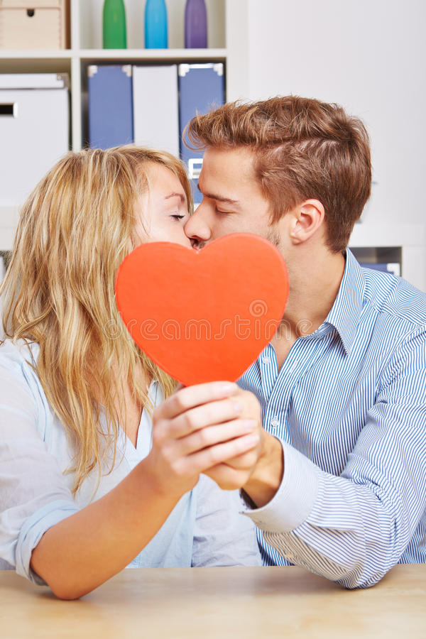 Couple kissing behind red heart. Young couple kissing hiding behind a big red heart in the living room stock image