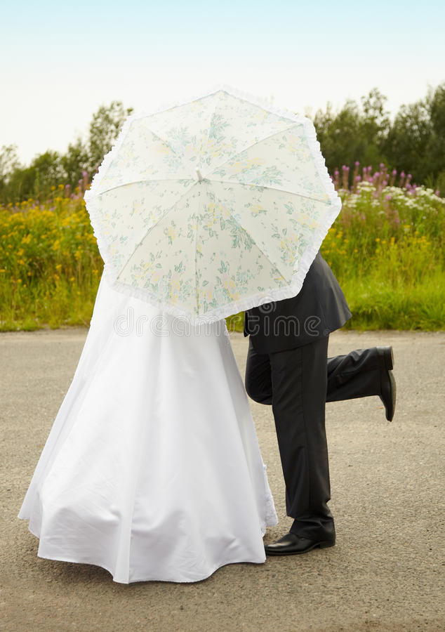 Couple kissing behind an umbrella royalty free stock photo