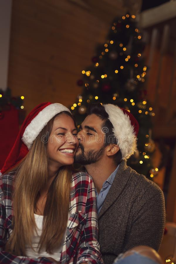Couple kissing by the Christmas tree. Couple in love wearing Santa hats, sitting by the beautifully decorated Christmas tree, kissing and having fun on Christmas stock photo