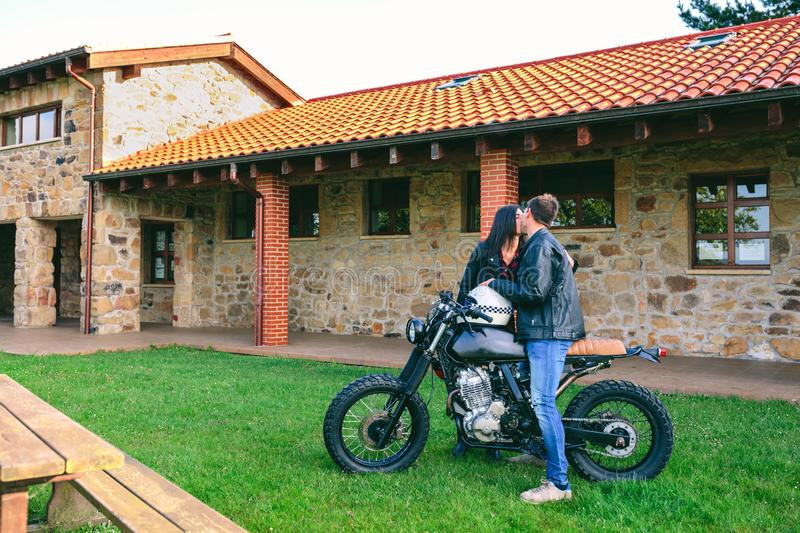 Couple kissing with custom motorcycle. Young couple kissing with custom motorcycle outdoors stock images