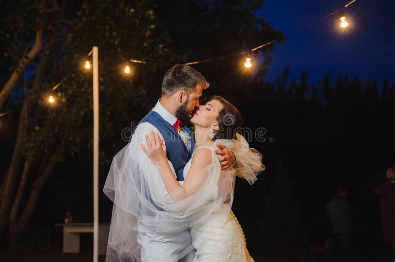 Couple kissing in evening street lights. Beautiful couple have romantic moment with cuddles and kisses in the end of wedding day. Couple kissing in evening royalty free stock photos