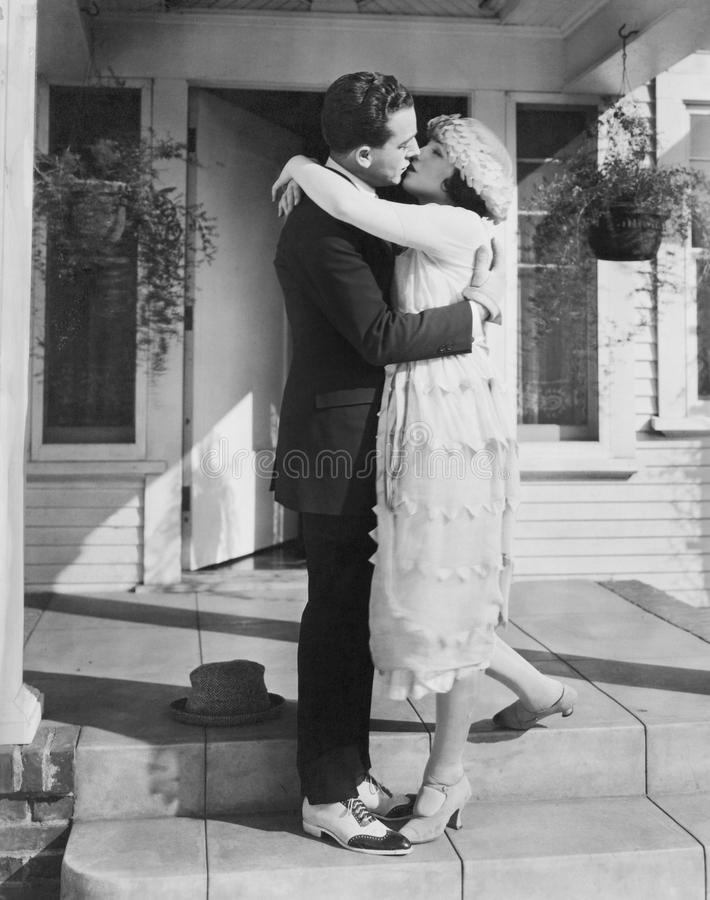 Couple kissing on front porch royalty free stock photography