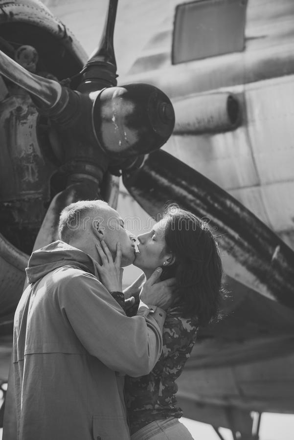 Couple kissing in front of propeller of old plane on sunny day. Couple in love full of desire hugs near airplane on. Background. Couple on excursion to museum stock photo