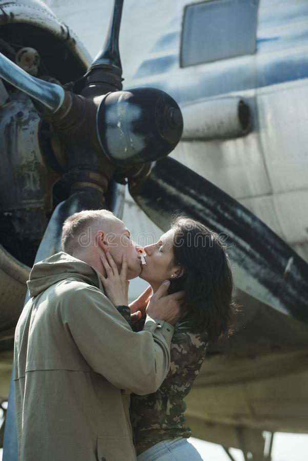 Couple kissing in front of propeller of old plane on sunny day. Couple in love full of desire hugs near airplane on. Background. Couple on excursion to museum stock image