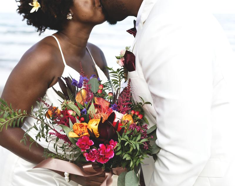 Couple kissing and holding bouquet stock photography
