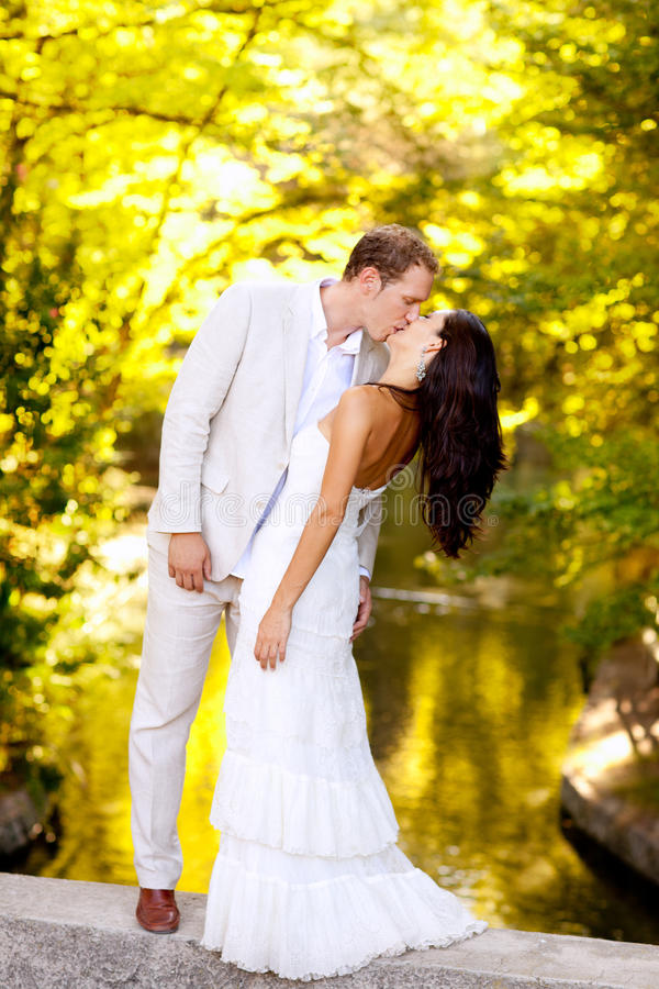 Couple kissing in honeymoon outdoor park stock photos