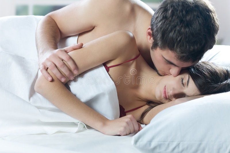 Download Couple Kissing And Hugging On The Bed In Bedroom Stock Photo