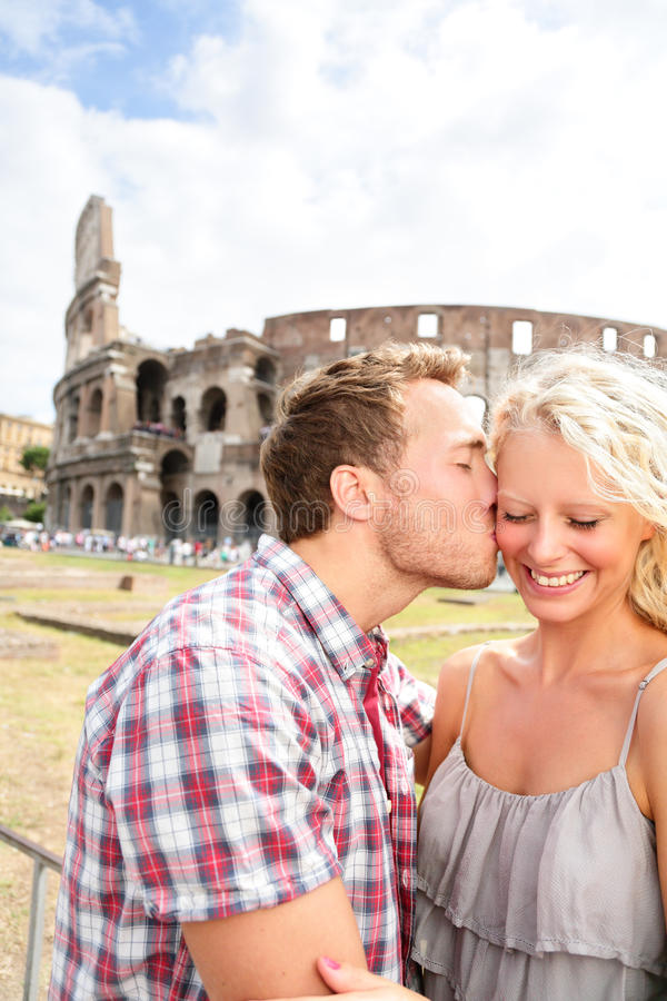 Couple kissing in love in Rome by the Colosseum. Romantic couple tourists having fun on holidays vacation and men kissing women on cheek. Beautiful blonde girl stock photos
