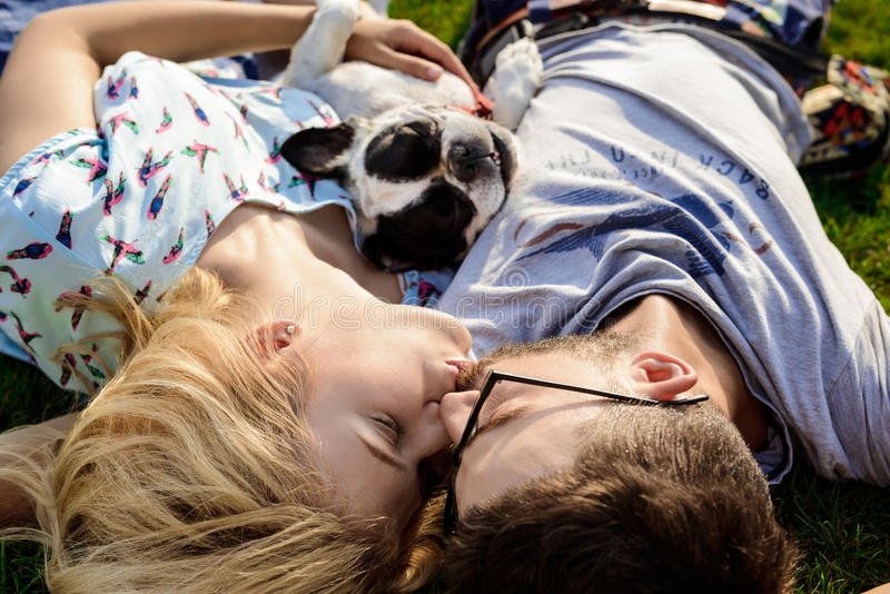 Couple kissing, lying with French bulldog on grass in park. stock photos