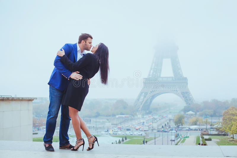 Couple kissing near Eiffel Tower in Paris, valentines day. Destination in Europe, city of love royalty free stock image