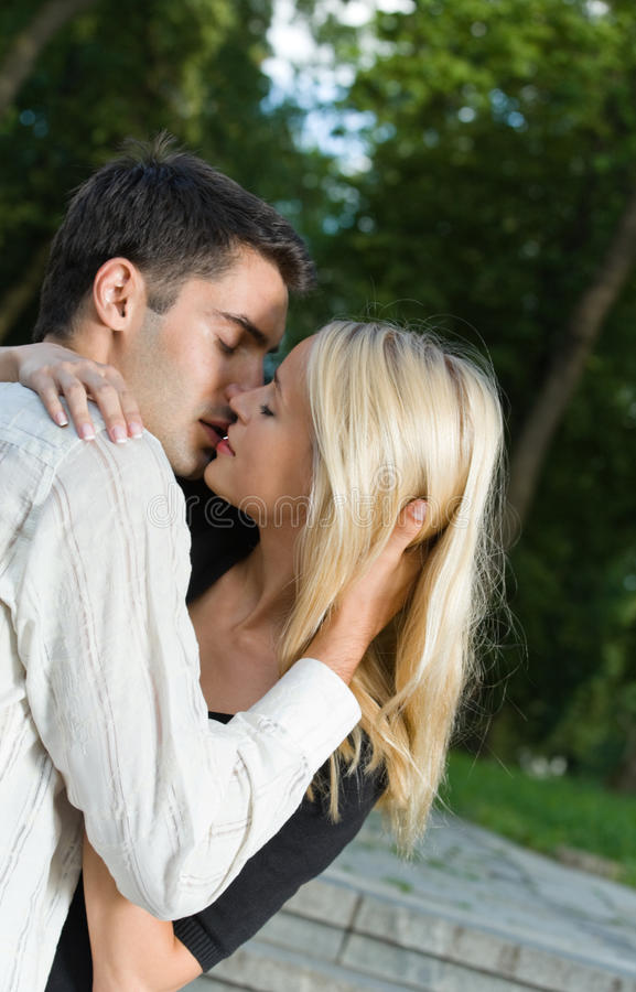 Couple kissing, outdoors. Young amorous couple kissing, outdoors stock photo