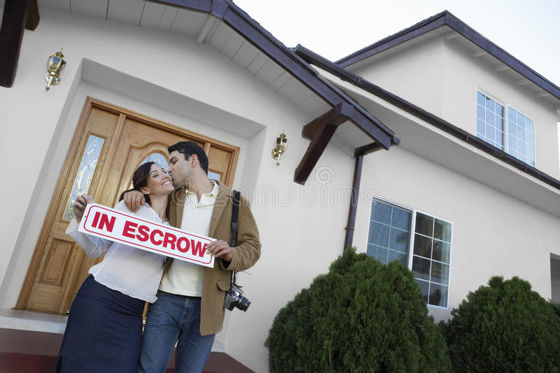 Couple Kissing Outside New House. Portrait of a happy couple kissing outside new house stock photography