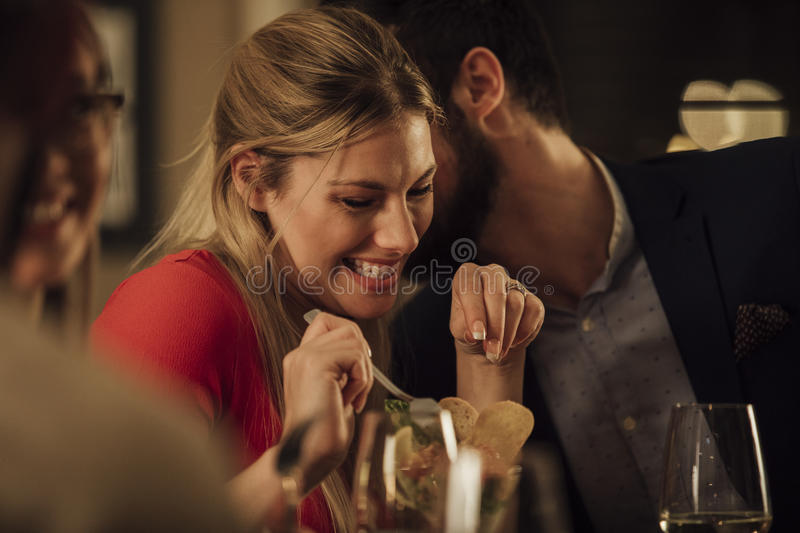 Couple Kissing In Restaurant. Couple are being romantic while having a meal in a restaurant. The men is kissing the women on on the cheek and she is giggling stock images