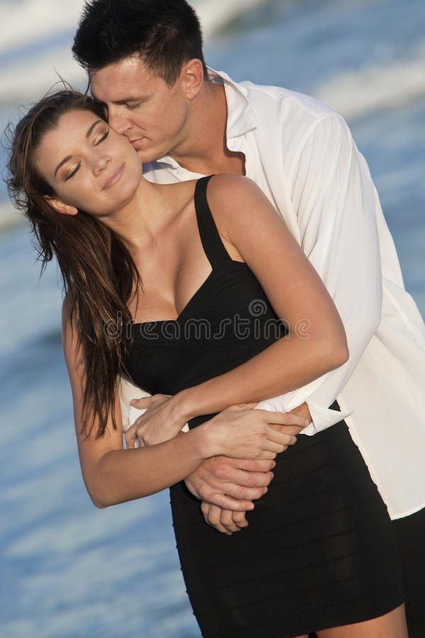 Couple Kissing In Romantic Embrace On Beach stock image