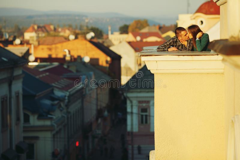 Couple kissing on the roof at sunset royalty free stock images