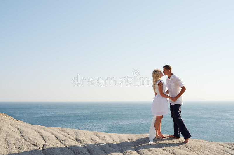 Couple kissing by the sea. While standing on a rock royalty free stock photos