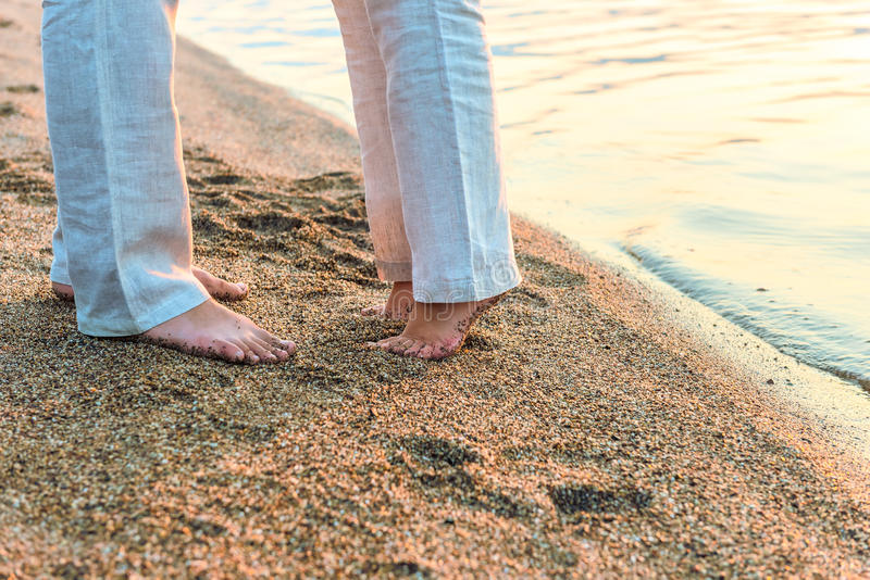 Couple kissing at the sea. Legs close up royalty free stock images