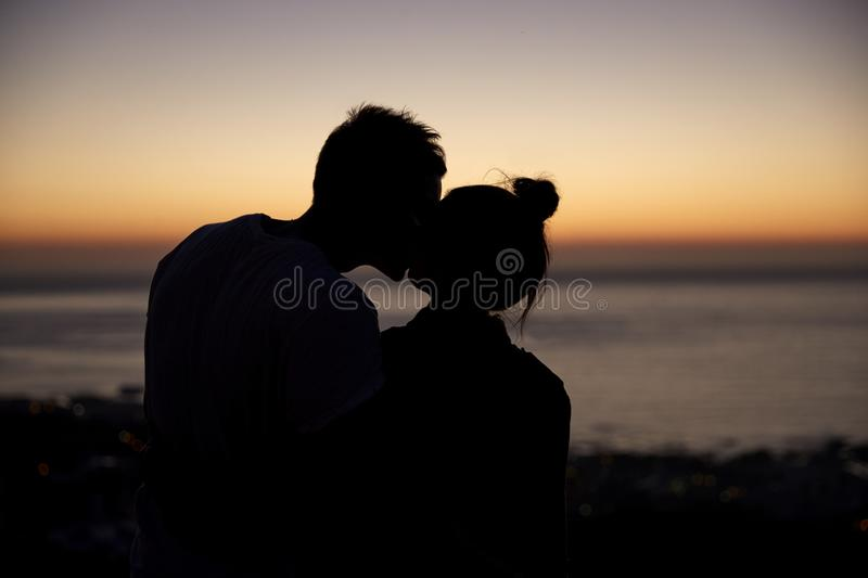 Couple kissing by the sea at sunset, silhouette royalty free stock images