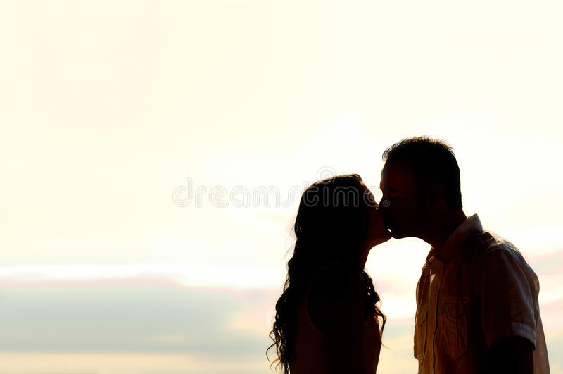 Couple kissing at sunset backlit. Silhouette of romantic young couple kissing at sunset backlit stock image