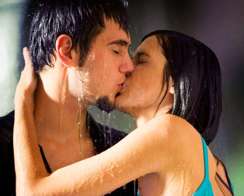 Couple kissing under a rain stock photos