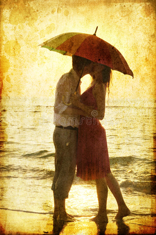 Couple kissing under umbrella stock photo
