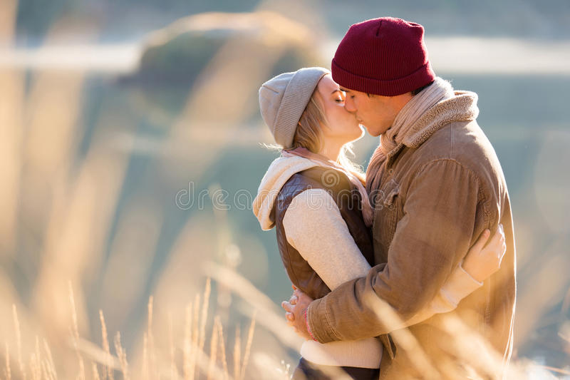 Couple kissing winter. Loving young couple kissing by the lake in winter morning stock image