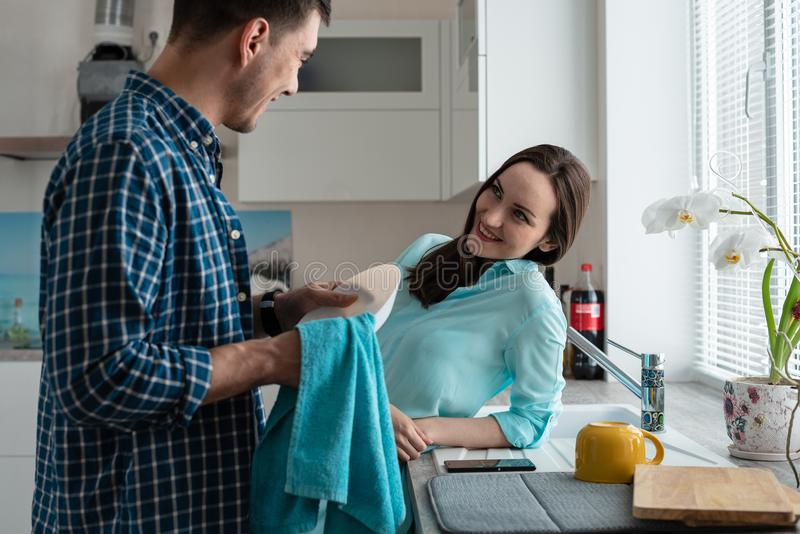 Couple in the kitchen interior have fun talking while washing dishes. authentic image side view stock image