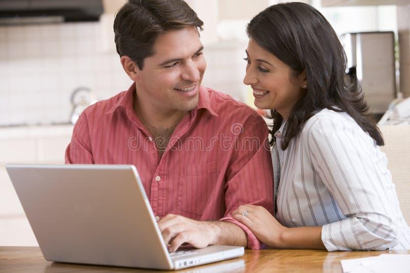 couple kitchen laptop smiling using