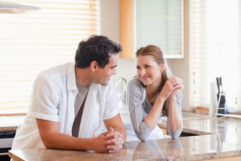Couple in the kitchen looking at each other royalty free stock photo