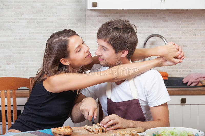 Couple at the kitchen. Romantic couple cooking together at the kitchen stock photos