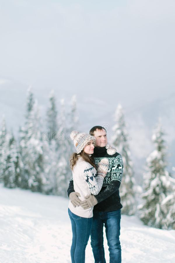 A couple in knitted clothes walks in winter in the forest with trees stock photography