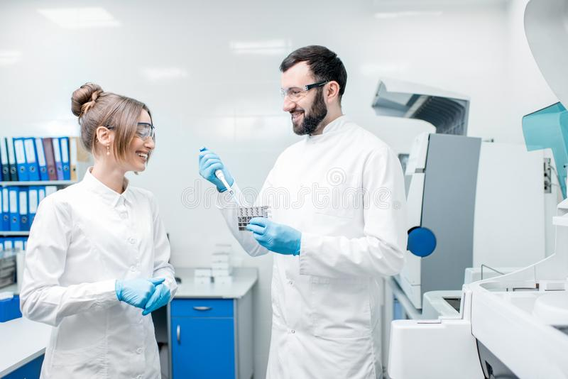 Laboratory assistants workign with test tubes. Couple of laboratory assistants in uniform working with test tubes standing near the analyzer machine in the royalty free stock images