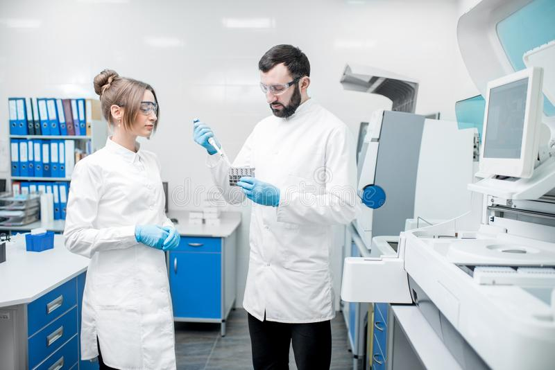 Laboratory assistants workign with test tubes. Couple of laboratory assistants in uniform working with test tubes standing near the analyzer machine in the stock photos