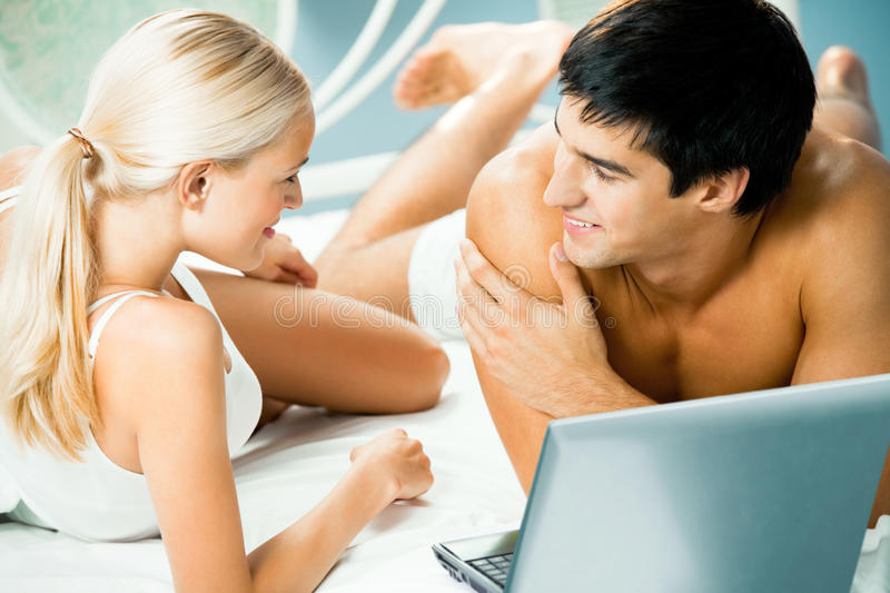 Couple with laptop. Couple working with laptop at bedroom royalty free stock photography