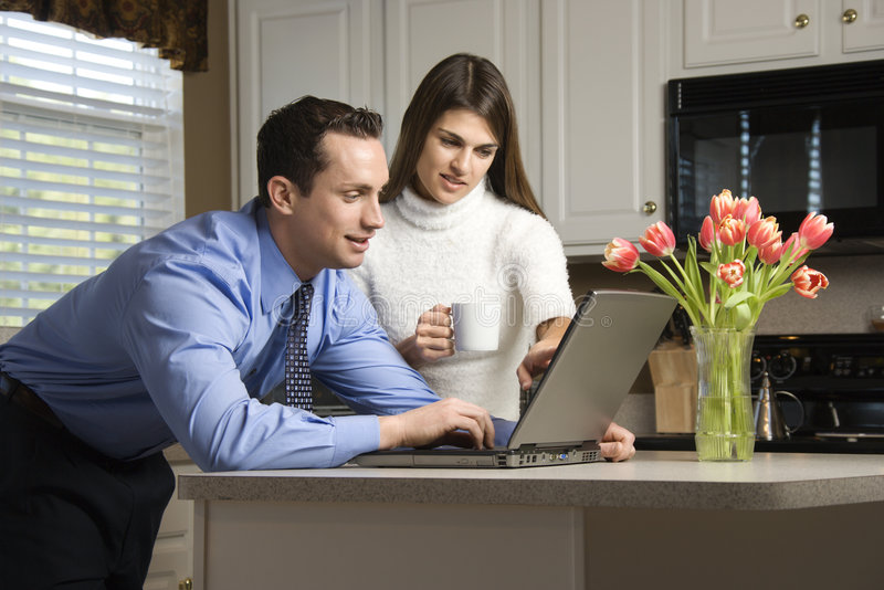 Couple with laptop. Caucasian couple in kitchen with coffee looking at laptop computer
