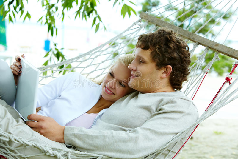 Couple with laptop. Happy dates with laptop lying in hammock royalty free stock images