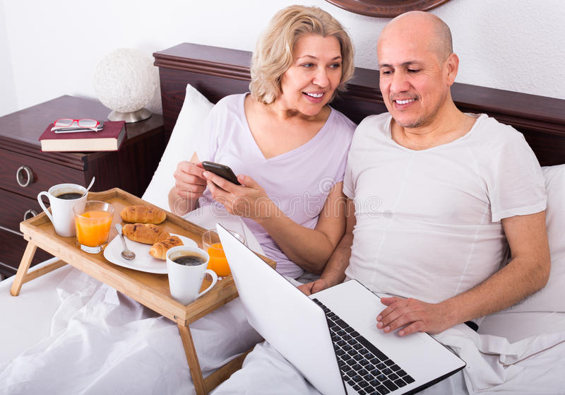 Couple with laptop during breakfast in bed. Happy men showing girlfriend something on laptop during breakfast royalty free stock image