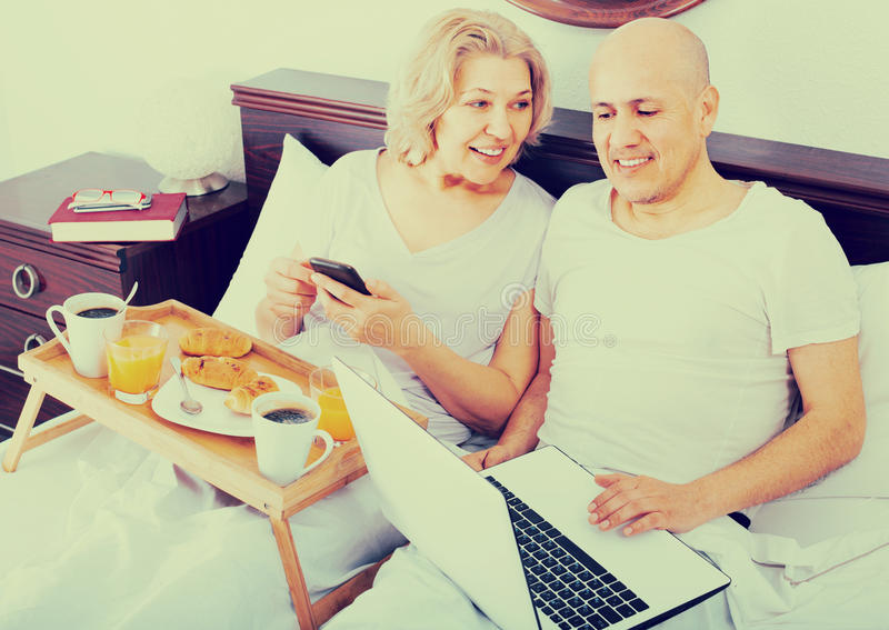 Couple with laptop during breakfast in bed. Happy men showing girlfriend something on laptop during breakfast stock photos