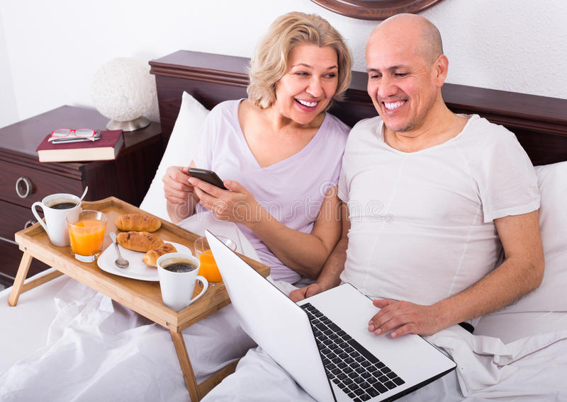 Couple with laptop during breakfast in bed. Smiling aged men showing mature girlfriend something on laptop during breakfast . Focus on man stock images