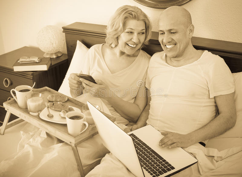 Couple with laptop during breakfast in bed. Smiling aged men showing mature girlfriend something on laptop during breakfast . Focus on man stock photo