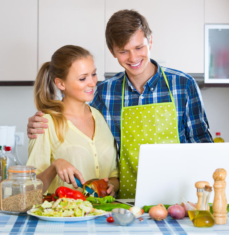 Couple with laptop at kitchen. Young men showing cooking housewife something on laptop screen royalty free stock image