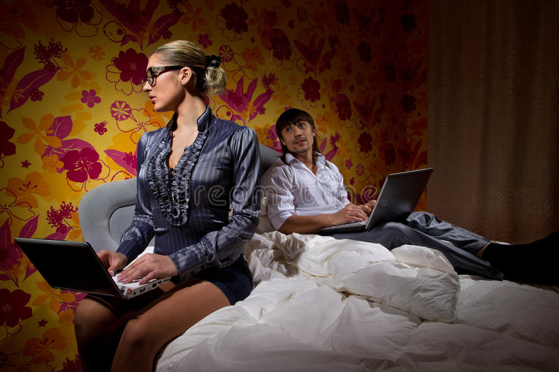 Couple with laptop lying on bed. Young couple with laptop lying on bed at home royalty free stock photos