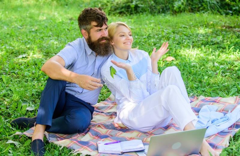 Couple with laptop relax natural environment. Family enjoy relax nature background. Couple bearded man and blonde woman royalty free stock image