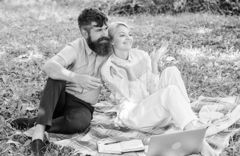Couple with laptop relax natural environment. Family enjoy relax nature background. Couple bearded man and blonde woman royalty free stock photos