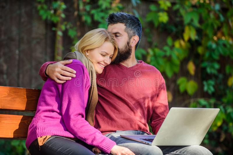 Couple with laptop sit bench in park nature background. Family surfing internet for interesting content. Internet. Surfing concept. Couple in love notebook stock photography