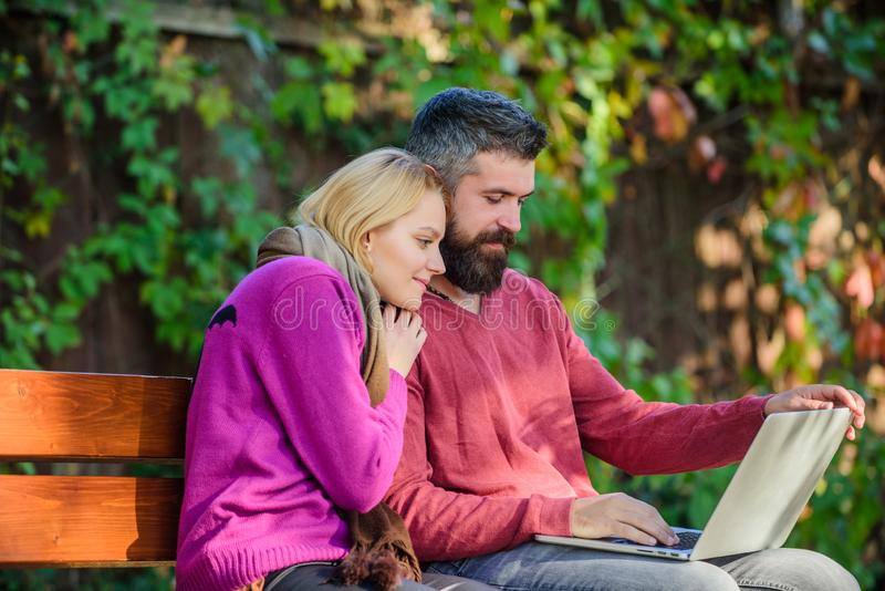 Couple with laptop sit bench in park nature background. Surfing internet together. Family surfing internet for. Interesting content. Couple in love notebook royalty free stock image