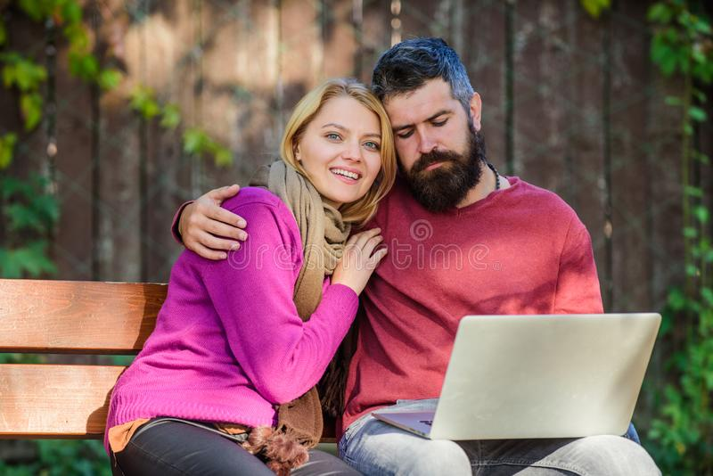 Couple with laptop sit bench in park nature background. Surfing internet together. Family surfing internet for. Interesting content. Internet surfing concept stock photography