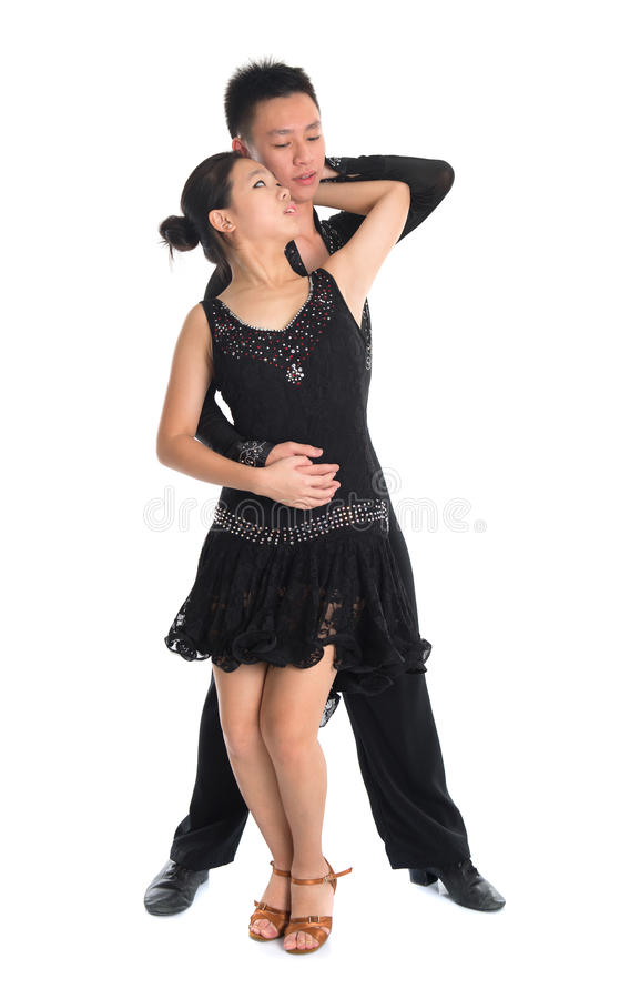 Couple Latin dancers dancing. Modern young Asian teens couple latin dancers dancing in front of the studio background, full length isolated white stock photography