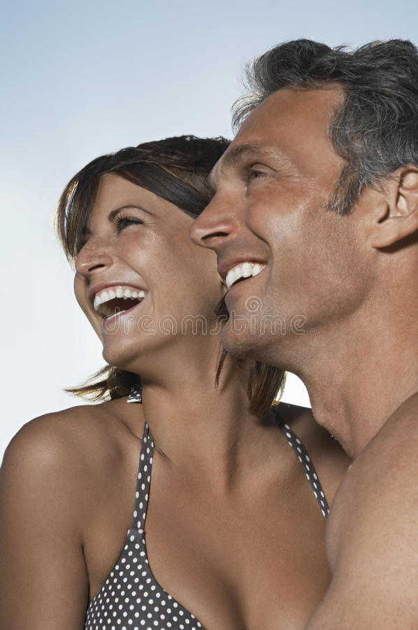 Couple Laughing Against Sky stock images